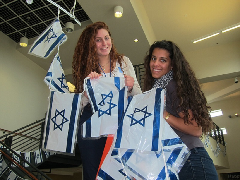 Past Chaverim decorate the Mayerson JCC with Israeli flags.